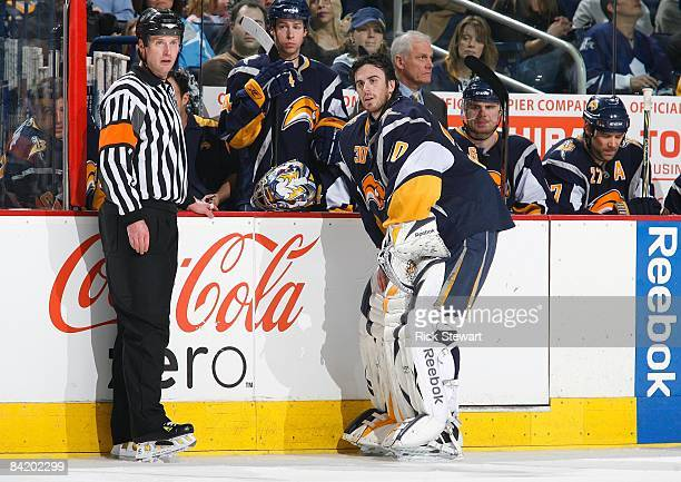 NHL referee Kevin Pollock and goaltender Ryan Miller of the Buffalo Sabres look on from the Sabres bench area during a break in NHL game between the...