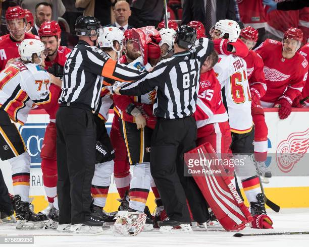 Referee Kevin Pollock and linesman Devin Berg try to break up a multi player fight in front of the benches during an NHL game at Little Caesars Arena...