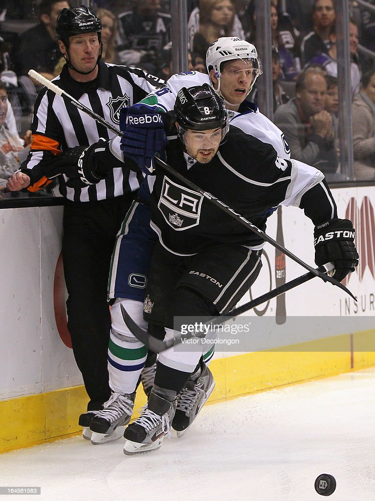 Referee Kevin Pollock looks on as Jannik Hansen #36 of the Vancouver Canucks holds back Drew Doughty #8 of the Los Angeles Kings as Doughty skates after the puck during the NHL game at Staples Center on March 23, 2013 in Los Angeles, California. The Canucks defeated the Kings 1-0.