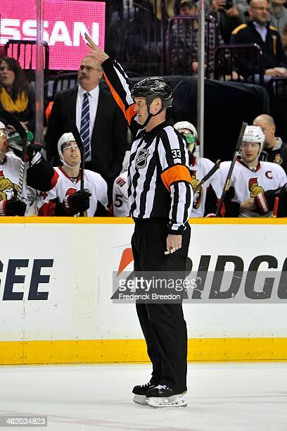 Referee Kevin Pollock officiates a game between the Ottawa Senators and the Nashville Predators at Bridgestone Arena on January 11 2014 in Nashville...