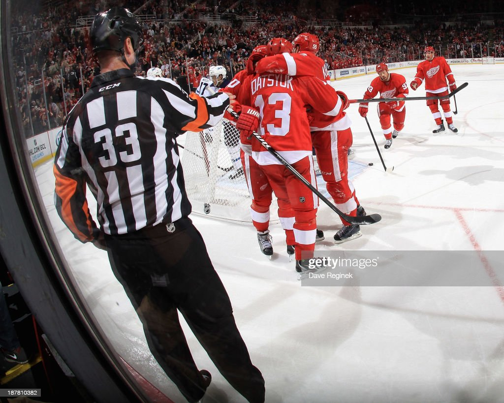 Referee Kevin Pollock #33 points at the net calling a goal as Henrik Zetterberg #40, Niklas Kronwall #55, Johan Franzen #93 and Daniel Alfredsson #11 of the Detroit Red Wings surround teammate Pavel Datsyuk #13 after scoring late in the third period during an NHL game against the Winnipeg Jets at Joe Louis Arena on November 12, 2013 in Detroit, Michigan.