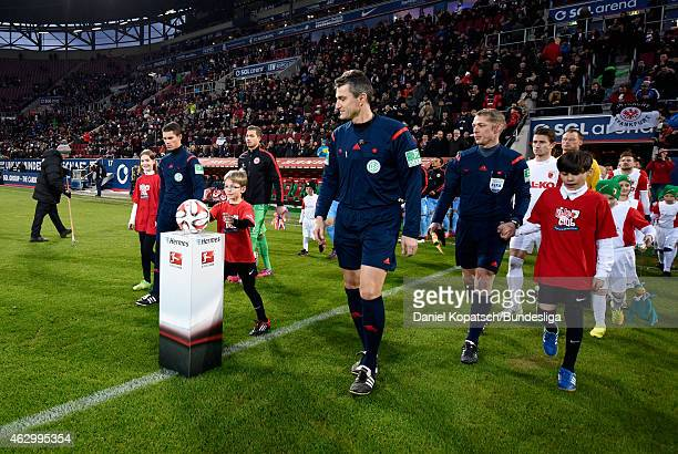 Referee Knut Kircher and players look on prior to the first Bundesliga match between FC Augsburg and Eintracht Frankfurt at SGL Arena on February 8...