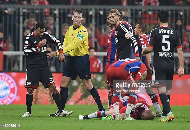 Referee Knut Kircher protects Karim Bellarabi of Leverkusen after his foul against Sebastian Rode of Muenchen during the Bundesliga match between FC...