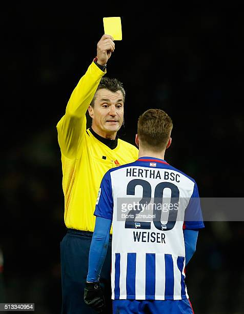 Referee Knut Kircher shows a yellow card to Mitchell Weiser of Berlin during the Bundesliga match between Hertha BSC and Eintracht Frankfurt at...