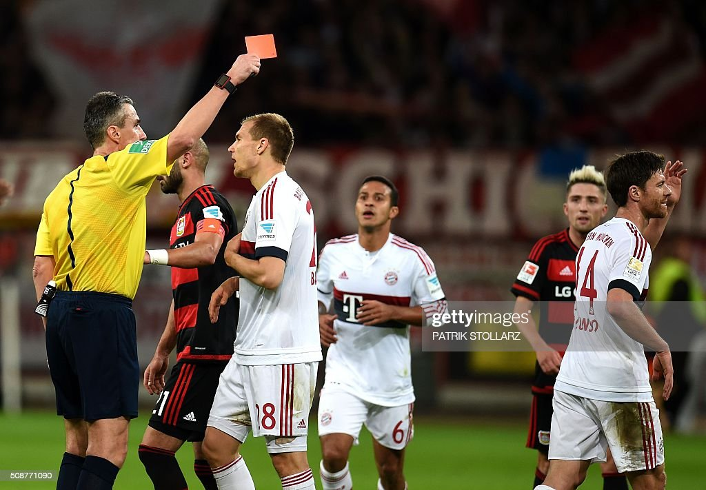 Referee Knut Kircher shows the red card to Bayern Munich's Spanish midfielder Xabi Alonso (R) during the German first division Bundesliga football match of Bayer 04 Leverkusen v Bayern Munich in Leverkusen, western Germany, on February 6, 2016. / AFP / PATRIK STOLLARZ /