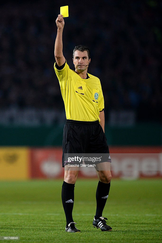 Referee Knut Kircher shows yellow card during DFB Cup second round match between Preussen Muenster and FC Augsburg at Preussenstadion on September 24, 2013 in Muenster, Germany.