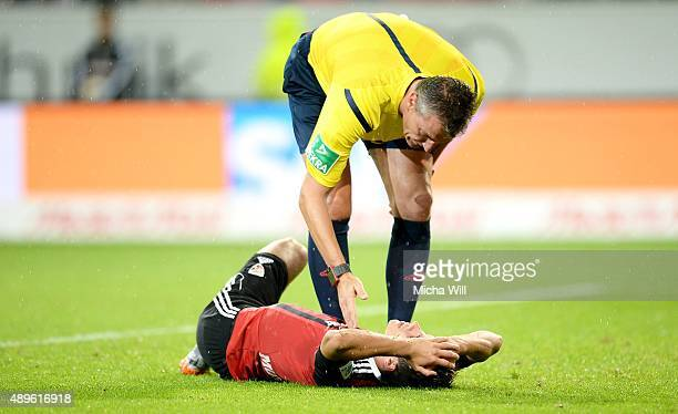 Referee Knut Kircher talks to Maurice Multhaup of Ingolstadt on the ground during the Bundesliga match between FC Ingolstadt and Hamburger SV at Audi...