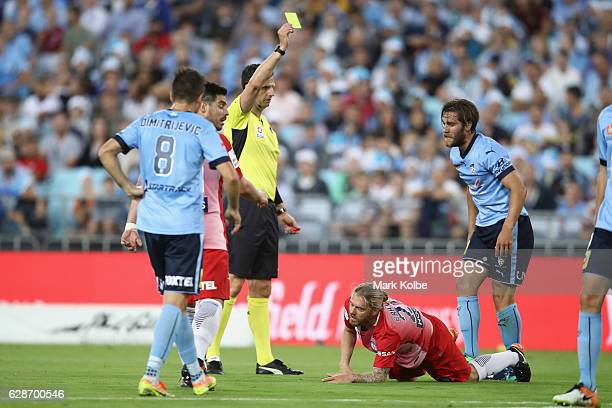Referee Kris GriffithJones shows a yellow card to Joshua Brillante of Sydney FC after a foul on Luke Brattan of Melbourne City during the round 10...