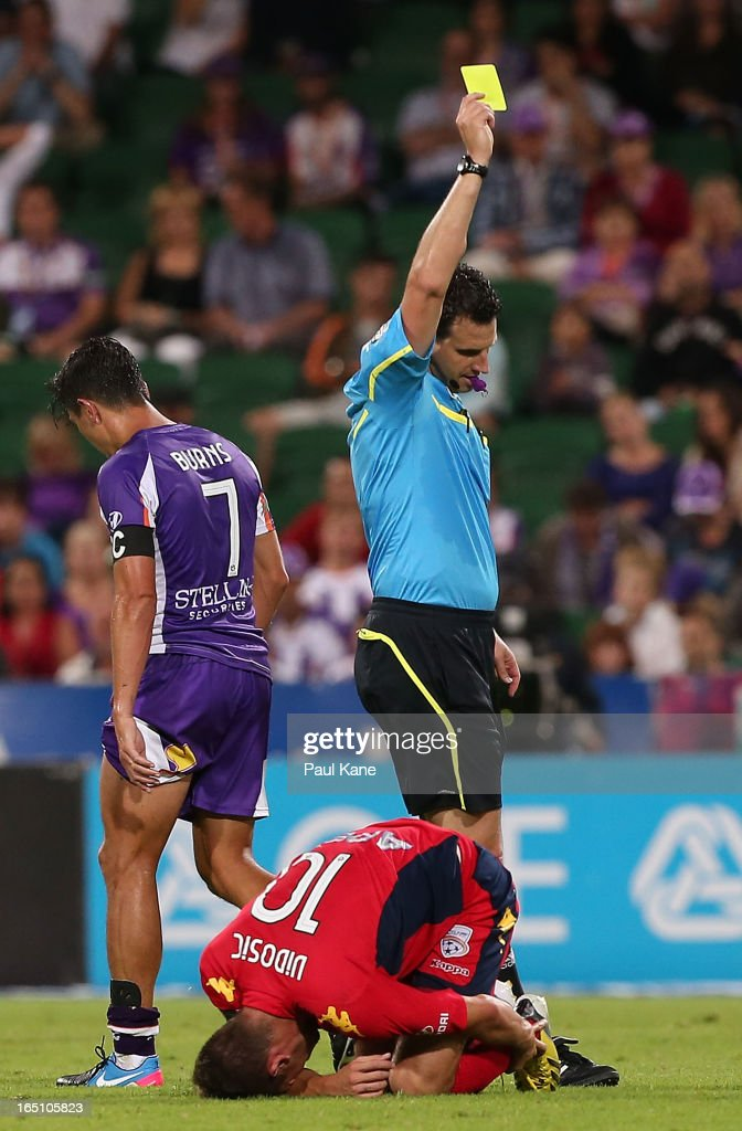 Referee Kris-Griffiths Jones issues <a gi-track='captionPersonalityLinkClicked' href=/galleries/search?phrase=Jacob+Burns&family=editorial&specificpeople=2178094 ng-click='$event.stopPropagation()'>Jacob Burns</a> of the Glory a yellow card after a tackle on Dario Vidosic of Adelaide during the round twenty seven A-League match between Perth Glory and Adelaide United at nib Stadium on March 30, 2013 in Perth, Australia.