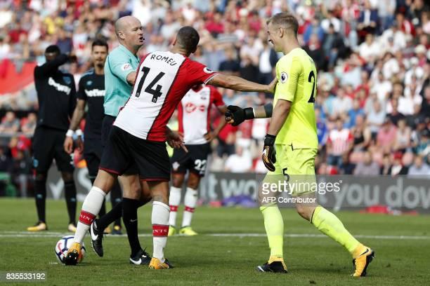Referee Lee Mason directs West Ham United's English goalkeeper Joe Hart to move the ball prior to Southampton's English striker Charlie Austin taking...