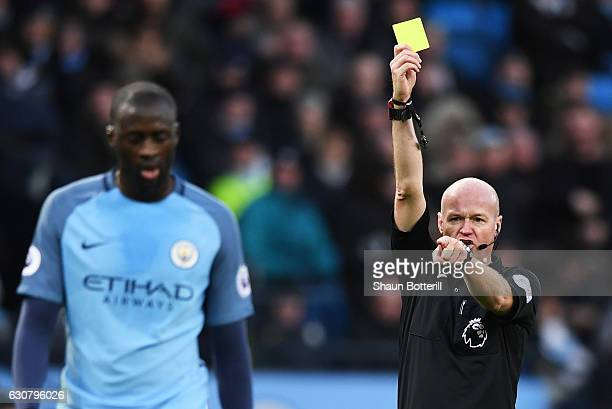 Referee Lee Mason shows Yaya Toure of Manchester City a yellow card during the Premier League match between Manchester City and Burnley at Etihad...