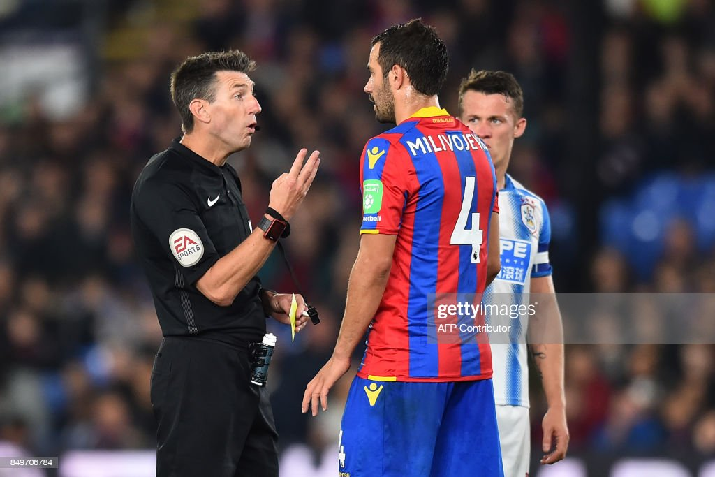 Referee Lee Probert speaks to Crystal Palace's Serbian midfielder Luka Milivojevic before giving him a yellow card during the English League Cup third round football match between Crystal Palace and Huddersfield Town at Selhurst Park in south London on September 19, 2017. / AFP PHOTO / Glyn KIRK / RESTRICTED TO EDITORIAL USE. No use with unauthorized audio, video, data, fixture lists, club/league logos or 'live' services. Online in-match use limited to 75 images, no video emulation. No use in betting, games or single club/league/player publications. /