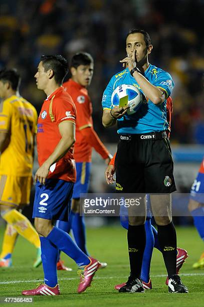 Referee Luis Enrique Santander asks Fausto Pinto of Cruz Azul to stop discussing during a match between Tigres UANL and Cruz Azul as part of the 10th...