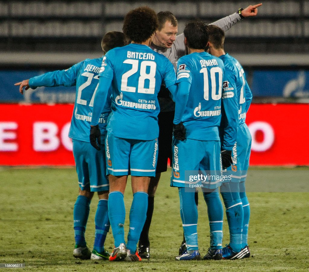 Referee Maksim Layushkin (C) is surrounded by FC Zenit St. Petersburg players after Miguel Danny of FC Zenit St. Petersburg #10 is sent off during the Russian Premier League match between FC Zenit St. Petersburg and FC Anzhi Makhachkala at the Petrovsky Stadium on December 10, 2012 in St. Petersburg, Russia.