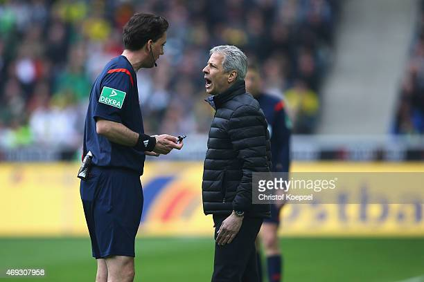 Referee Manuel Graefe and head coach Lucien Favre of Moenchengladbach discuss during the Bundesliga match between Borussia Moenchenglkadbach and...