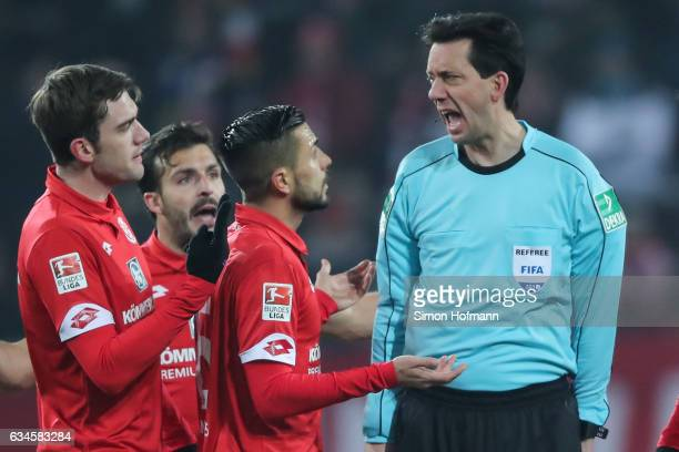 Referee Manuel Graefe argues with tem mates of Mainz during the Bundesliga match between 1 FSV Mainz 05 and FC Augsburg at Opel Arena on February 10...