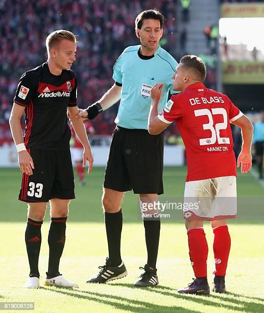 Referee Manuel Graefe discusses with Pablo de Blasis of Mainz and Florent Hadergjonaj of Ingolstadt during the Bundesliga match between 1 FSV Mainz...