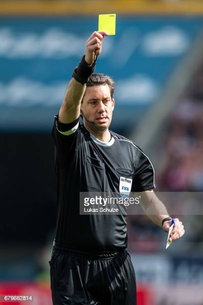 Referee Manuel Graefe holds the yellow card during the Bundesliga match between Eintracht Frankfurt and VfL Wolfsburg at CommerzbankArena on May 6...