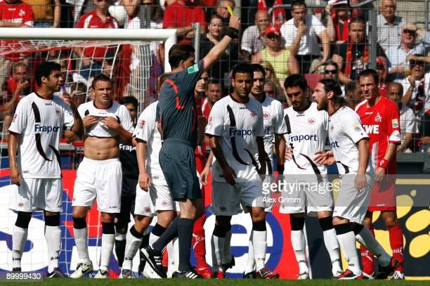 Referee Manuel Graefe shows a yellow card to Ioannis Amanatidis of Frankfurt during the Bundesliga match between 1 FC Koeln and Eintracht Frankfurt...