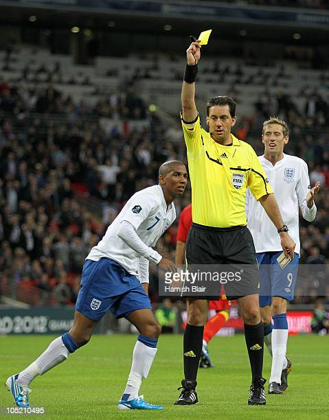 Referee Manuel Grafe shows Ashley Young of England a yellow card for diving during the UEFA EURO 2012 Group G Qualifying match between England and...