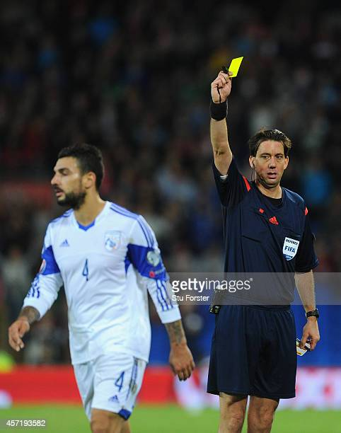 Referee Manuel Grafe yellow cards Giorgos Merkis of Cyprus during the EURO 2016 Qualifier match between Wales and Cyprus at Cardiff City Stadium on...