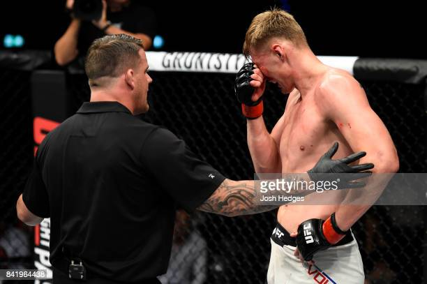 Referee Marc Goddard speaks with Alexander Volkov of Russia after receiving a poke to the eye from Stefan Struve of The Netherlands in their...