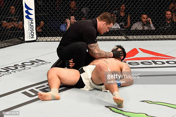 Referee Marc Goddard tends to Frank Mir of the United States as he lies on the Octagon mat after being defeated by Mark Hunt of New Zealand by KO in...