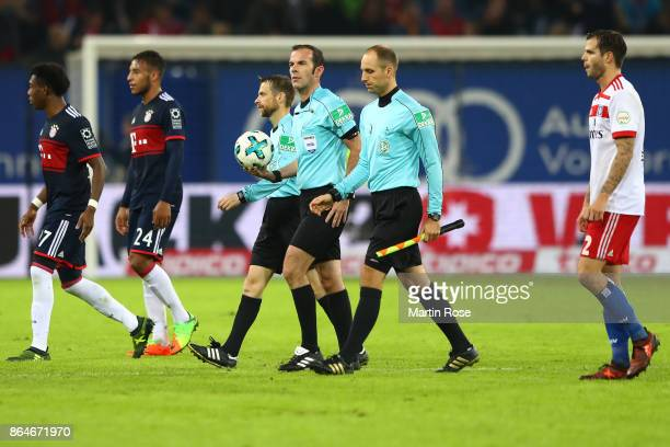 Referee Marco Fritz and assistant referees Dominik Schaal and Marcel Pelgrim leave the pitch at half time during the Bundesliga match between...