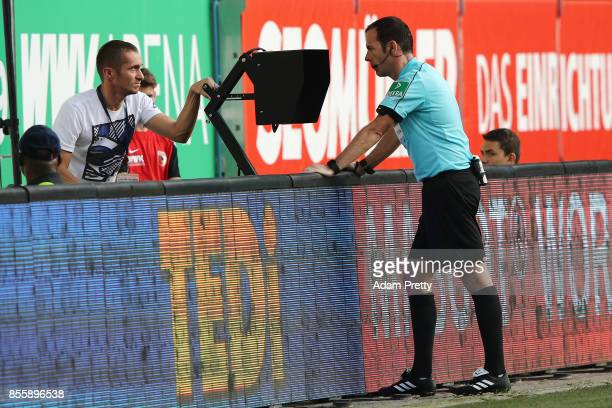 Referee Marco Fritz at the side to check with video referee during the Bundesliga match between FC Augsburg and Borussia Dortmund at WWKArena on...