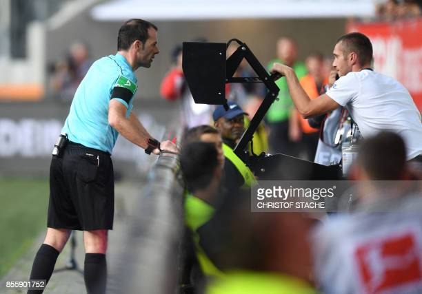Referee Marco Fritz checks the Video assistant referee during the German first division Bundesliga football match between FC Augsburg and Borussia...