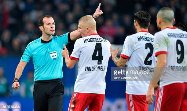 Referee Marco Fritz reacts as Hamburg players plead with him after Hamburg's German defender Gideon Jung took down Bayern Munich's French forward...