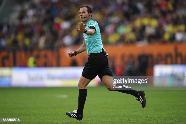 Referee Marco Fritz runs to the side to check with video referee during the Bundesliga match between FC Augsburg and Borussia Dortmund at WWKArena on...