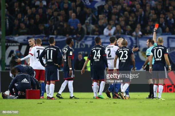 Referee Marco Fritz shows a red card to Gideon Jung of Hamburg following a foul on Kingsley Coman of Bayern Muenchen during the Bundesliga match...