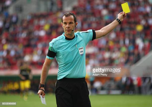 Referee Marco Fritz shows a yellow card during the Bundesliga match between FC Augsburg and Borussia Dortmund at WWKArena on September 30 2017 in...