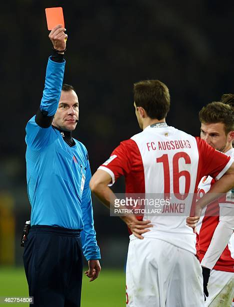 Referee Marco Fritz shows the red card to Augsburg's defender Christoph Janker during the German first division Bundesliga football match Borussia...