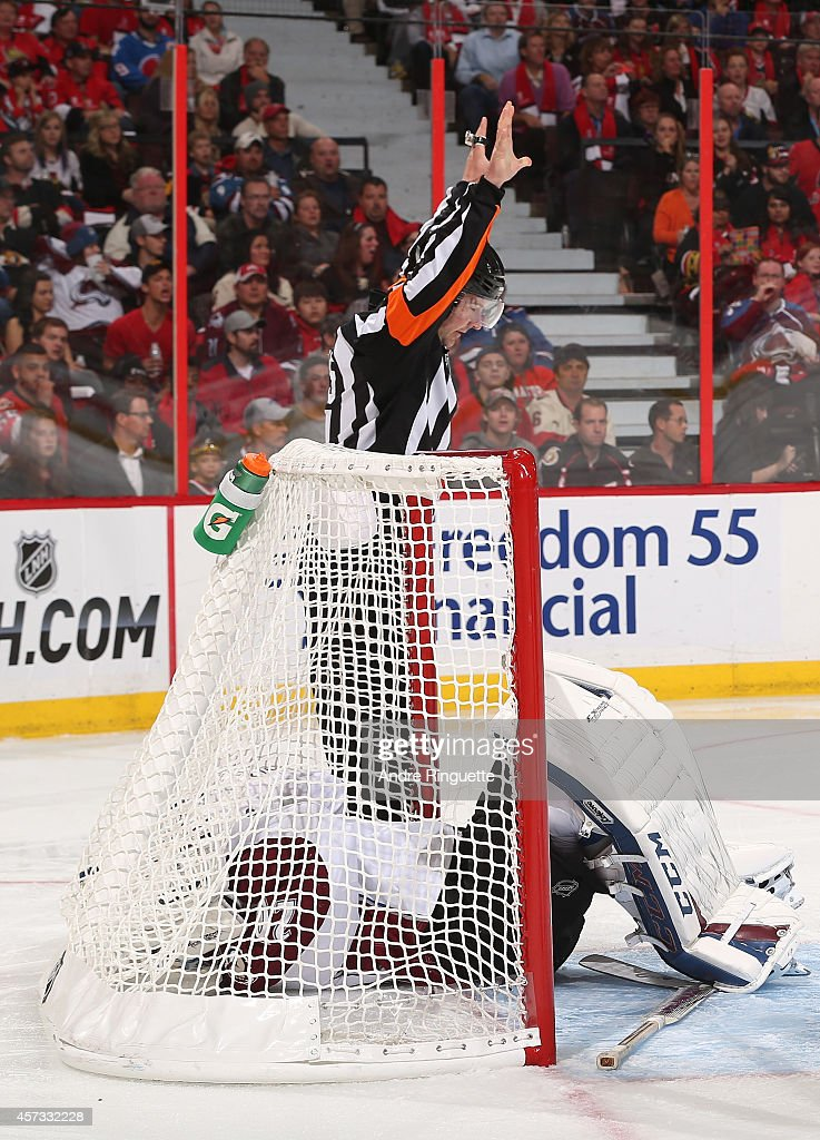 Referee Marcus Vinnerborg calls the play dead as goaltender Reto Berra of the Colorado Avalanche lies injured in his net after a first period...