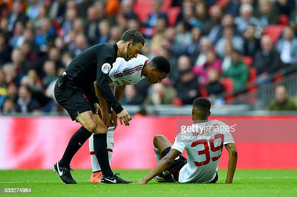 Referee Mark Clattenburg and Anthony Martial of Manchester United stand over an injured Marcus Rashford of Manchester United is given assistance...