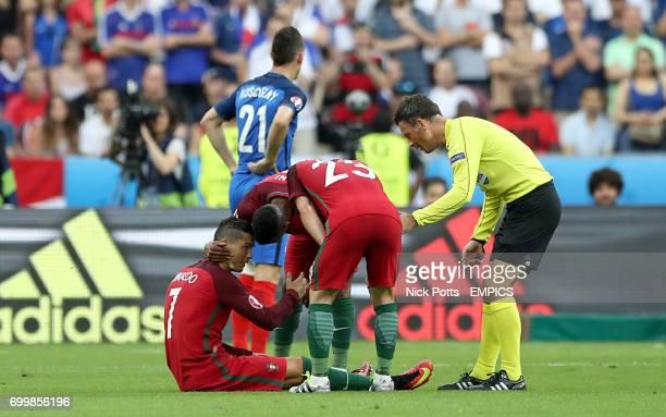 Referee Mark Clattenburg and Portugal's Nani and Sebastien Adrien Silva gather around Portugal's Cristiano Ronaldo after he goes down injured