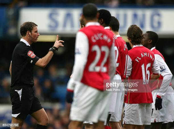 Referee Mark Clattenburg attempts to control Arsenal players
