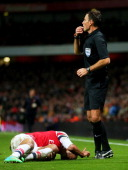 Referee Mark Clattenburg calls for the stretcher as Theo Walcott of Arsenal lies injured in the pitch during the Budweiser FA Cup third round match...