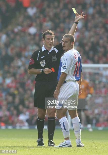 Referee Mark Clattenburg gives Blackburn's David Bentley a yellow card after a foul on Liverpool's John Arne Riise