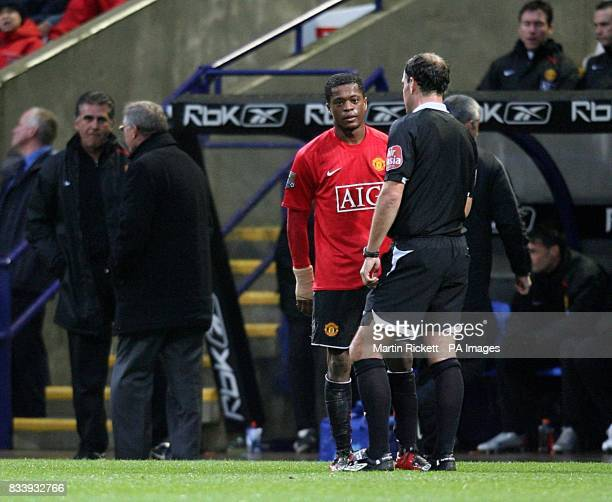 Referee Mark Clattenburg has a word with Manchester United's Patrice Evra as manager Alex Ferguson is sent to the stands