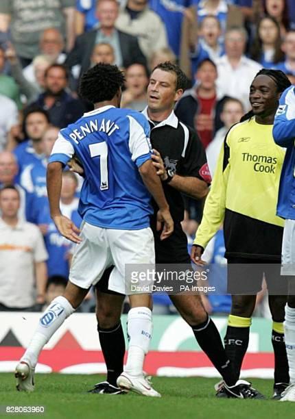 Referee Mark Clattenburg holds back Birmingham City's Jermaine Pennant from Manchester City's Kiki Musampa