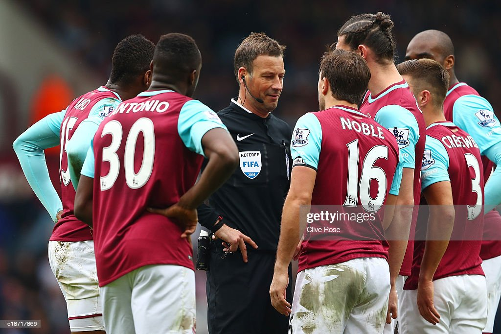 Referee Mark Clattenburg is surrounded by West Ham players after sending off Cheikhou Kouyate during the Barclays Premier League match between West Ham United and Crystal Palace at the Boleyn Ground on April 2, 2016 in London, England.