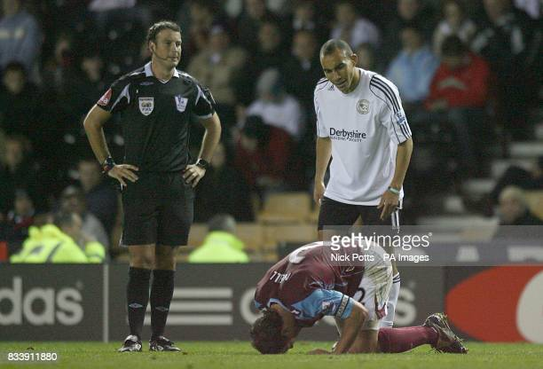 Referee Mark Clattenburg looks on as Derby County's Craig Fagan is frustrated with West Ham United's Lucas Neill reaction to a challenge
