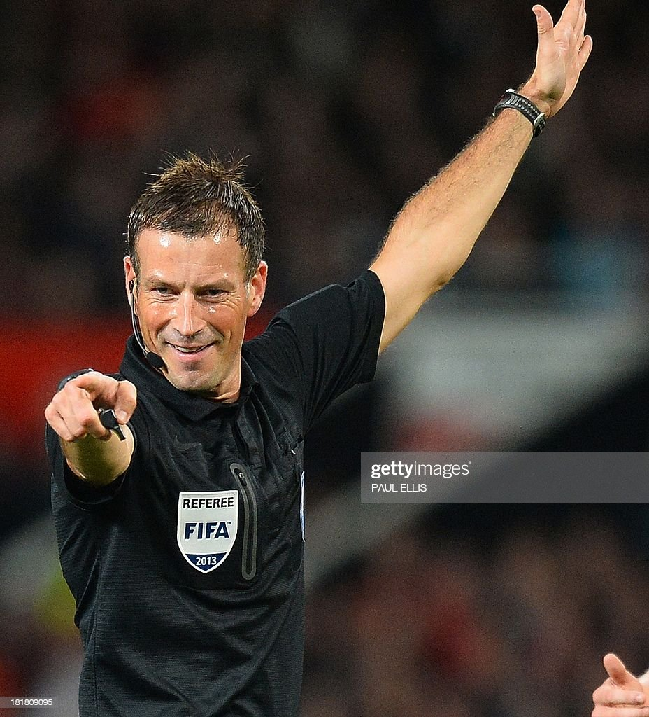 Referee Mark Clattenburg points during the League Cup football match between Manchester United and Liverpool at Old Trafford in Manchester on September 25, 2013.