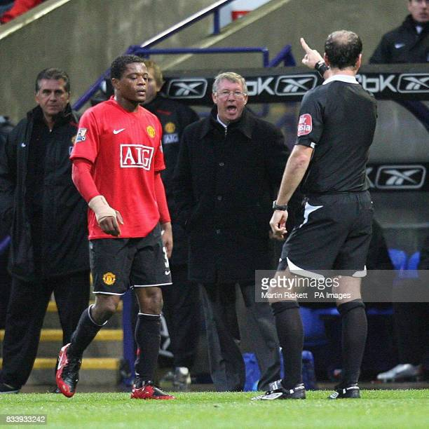 Referee Mark Clattenburg points to Alex Ferguson as he has words with Patrice Evra during the Barclays Premier League match at the Reebok Stadium...