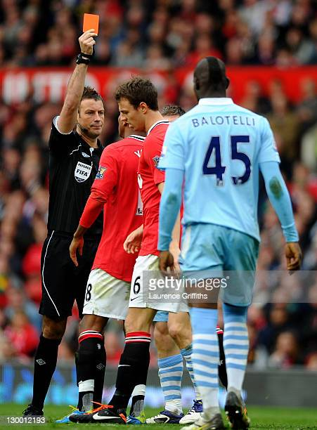 Referee Mark Clattenburg shows a red card to Jonny Evans of Manchester United during the Barclays Premier League match between Manchester United and...