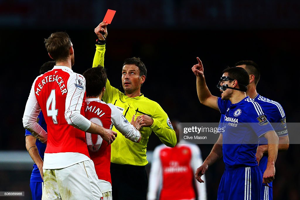 Referee Mark Clattenburg shows a red card to Per Mertesacker of Arsenal during the Barclays Premier League match between Arsenal and Chelsea at Emirates Stadium on January 24, 2016 in London, England.