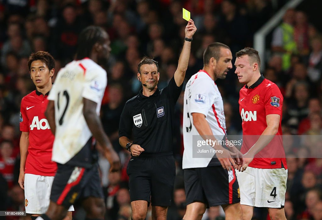 Referee Mark Clattenburg shows a yellow card during the Capital One Cup Third Round match betwen Manchester United and Liverpool at Old Trafford on September 25, 2013 in Manchester, England.